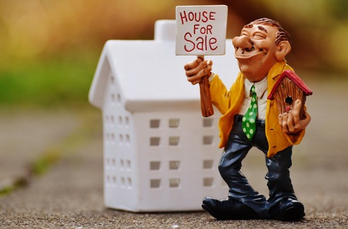 Illustration of a man holding House for Sale sign